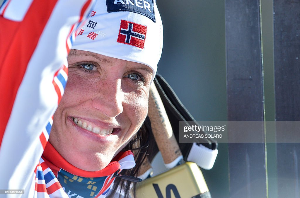 Norway's Marit Bjoergen smiles to her supporters on March 2, 2013 from the finish area after coming in first at the Women's Cross Country 30 km Classic race of the FIS Nordic World Ski Championships at Val Di Fiemme Cross Country stadium in Cavalese, northern Italy. AFP PHOTO / ANDREAS SOLARO