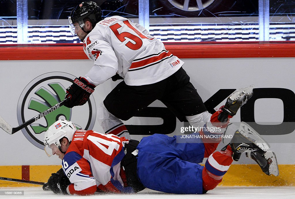 Norway's Mathis Olimb and Switzerland's Philippe Furrer (top) vie for the puck during the preliminary round match Norway vs Switzerland at the 2013 IIHF Ice Hockey World Championships on May 12, 2013 in Stockholm.
