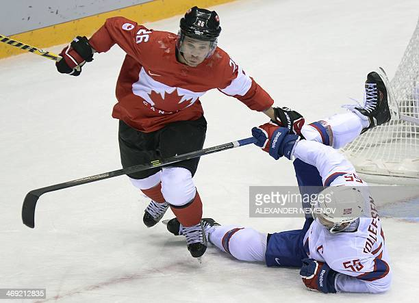 Norway's Olekristian Tollefsen vies with Canada's Matrin StLouis during the Men's Ice Hockey Group B match between Canada and Norway at the Sochi...