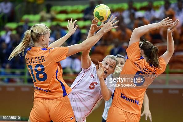 TOPSHOT Norway's pivot Heidi Loke vies with Netherlands' left back Kelly Dulfer and Netherlands' right back Laura van der Heijden during the women's...