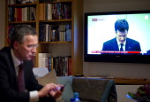 Norway's Prime Minister Jens Stoltenberg checks emails on his phone while a press conference by Statoils CEO Helge Lund is displayed on TV at his...