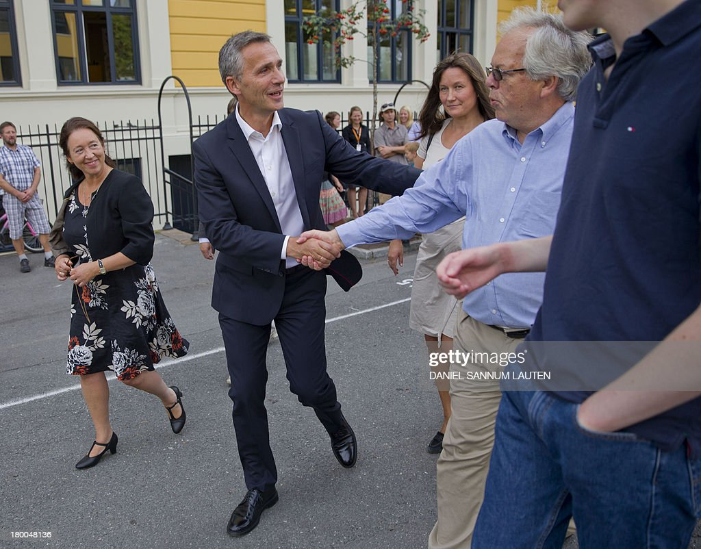 Norway's Prime Minister Jens Stoltenberg (C) speaks to a man as he and his wife Ingrid Schulerud leave a polling station in Oslo, on September 8, 2013. Norway's centre-right opposition looks set to oust Prime Minister Jens Stoltenberg in Monday's general election, paving the way for an anti-immigration party to enter government two years after right-wing extremist Anders Behring Breivik's deadly attacks. AFP PHOTO / DANIEL SANNUM LAUTEN