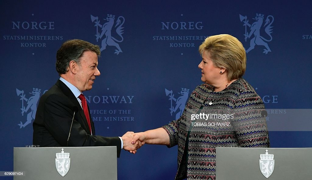 Norway's Prime Ministers Erna Solberg shakes hands with this year's Nobel Peace Prize laureate Colombian President Juan Manuel Santos after they addressed a news conference following talks at the government's guest house in Oslo on December 11, 2016. President Juan Manuel Santos were awarded this year's Nobel Peace Prize for his efforts to bring Colombias more than 50-year-long civil war to an end. / AFP / TOBIAS