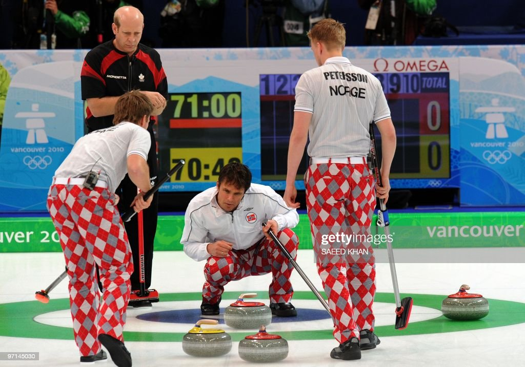 Norway's skip Thomas Ulsrud examine the stone formation inside a circle next to his teammate sweepers as Canada's skip Kevin Martin look on during...