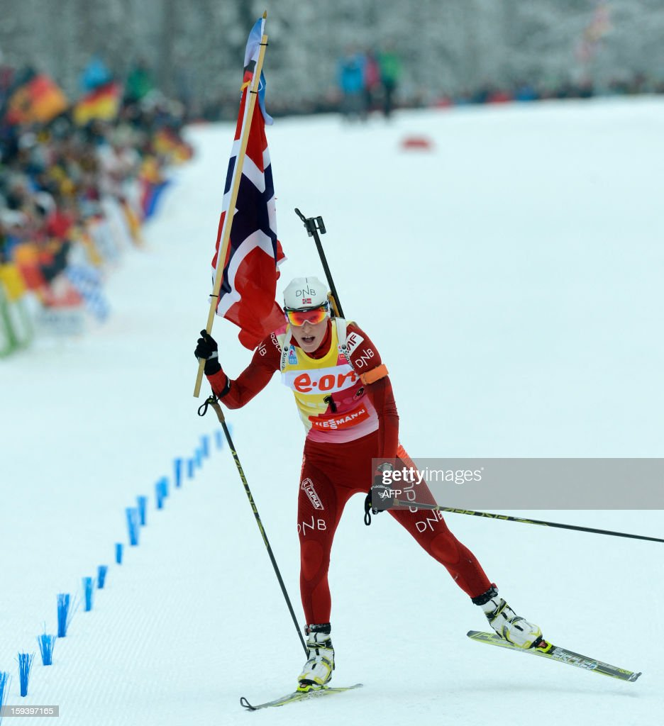 Norway's Tora Berger celebrates with the Norwegian flag after she arrived at the finish after the 12,5 km women Biathlon World Cup mass start competition on January 13, 2013, in Ruhpolding, southern Germany. Tora Berger won the competition, Belarus Darya Domracheva placed second and Russia's Olga Zaitseva placed third.