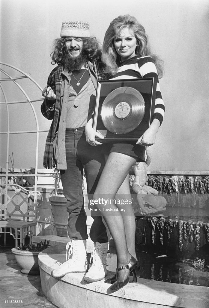 Norwegian actress Julie Ege (1943 - 2008) awards a gold disc to Jethro Tull singer and flautist <a gi-track='captionPersonalityLinkClicked' href=/galleries/search?phrase=Ian+Anderson&family=editorial&specificpeople=615834 ng-click='$event.stopPropagation()'>Ian Anderson</a> on the roof of the Dorchester Hotel, London, 19th February 1972. The disc is for over a million sales of their third album 'Benefit'.