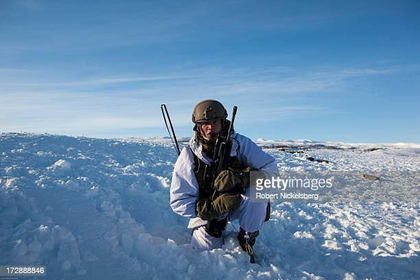 Norwegian army soldier observes a live fire exercise March 6 2013 during a 8 F degree windblown day in Skjold Norway White camouflage uniforms do not...