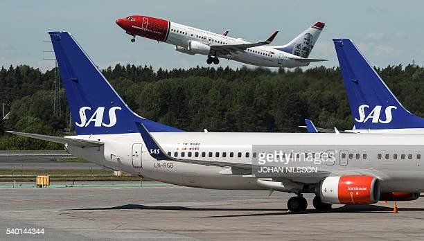 A Norwegian Boeing 737800 takes off behind the tails of two of Scandinavian airline Boeing 737 aircrafts parked at Terminal 4 during the SAS pilots...