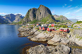 Norwegian fishing village  at the Lofoten Islands in Norway. Dramatic sunset clouds moving over steep mountain peaks.