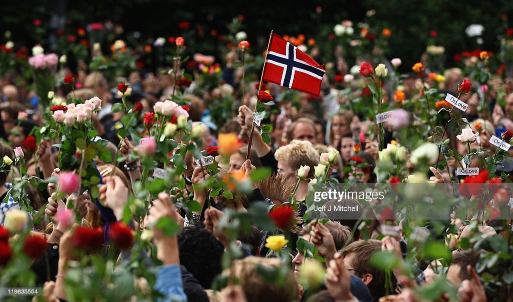 A Norwegian flag is held up amidst flowers as an estimated 100,000 people gather in Oslo town centre for a vigil following Friday's twin extremist attacks on July 25, 2011 in Oslo, Norway. Anders Behring Breivik, 32, claimed that he has 'two more cells' working with him as he appeared in court today following a bomb blast at a government building in Oslo and a shooting massacre on nearby Utoya Island that killed at least 76 people in all. The death toll was originally reported as 93. Breivik has been detained for eight weeks, four of which in full isolation.