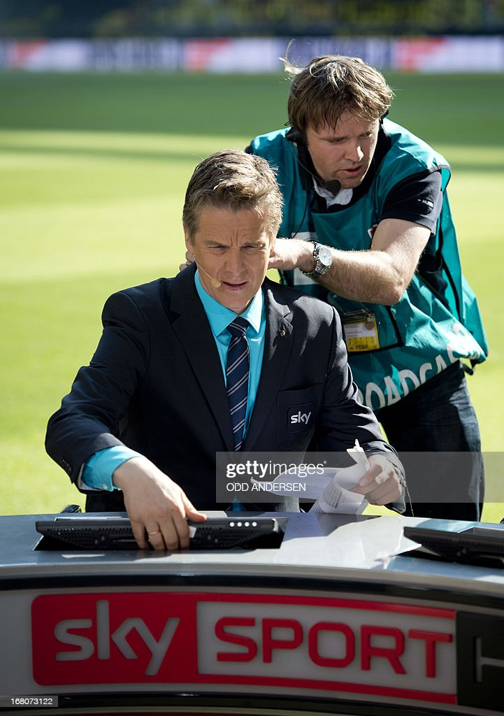 Norwegian Football pundit and ex Bundesliga player Jan Age Fjoertoft (L) has a microphone fitted as German pay tv broadcaster SKY are broadcasting pitch side prior to the German first division Bundesliga football match BVB Borussia Dortmund vs FC Bayern Munich in Dortmund, western Germany on May 4, 2013. The match ended in a 1-1 draw.