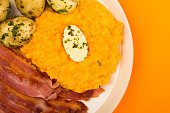 Norwegian Pork or Crispy Bacon With Mashed Swede and Boiled Potatoes Meal Against an Orange Background