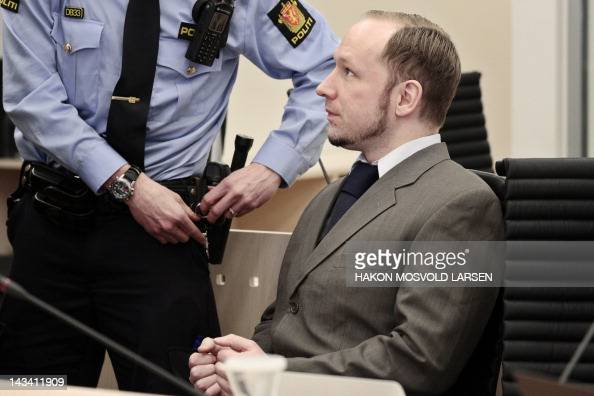 Norwegian rightwing extremist Anders Behring Breivik who killed 77 people in twin attacks in Norway last year waits for a police officer to remove...