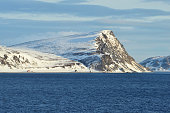 Norwegian Sea and island coast with buildings, Mageroya island, Finnmark County, Norway