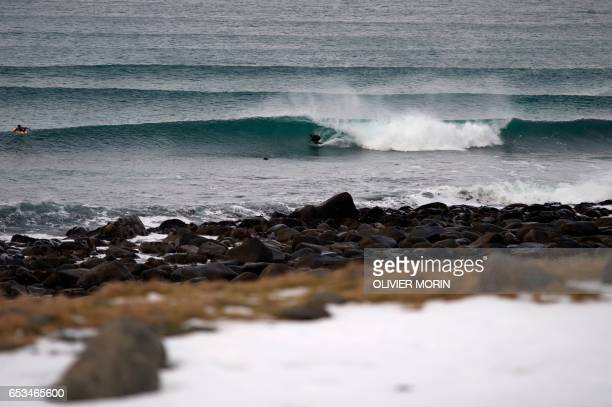 Norwegian surfer Espen Evertsen rides a wave at Unstad along the northern Atlantic Ocean on March 12 where the water temperatures is at five degrees...