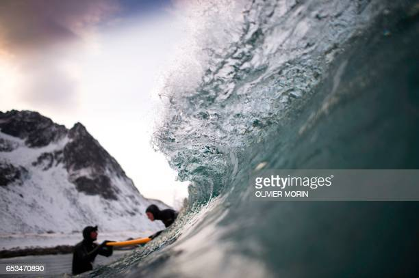 Norwegian surfer Tommy Olsen is seen in the water as he gives a surfing lesson to beginners in Flakstad near Unstad along the northern Atlantic Ocean...