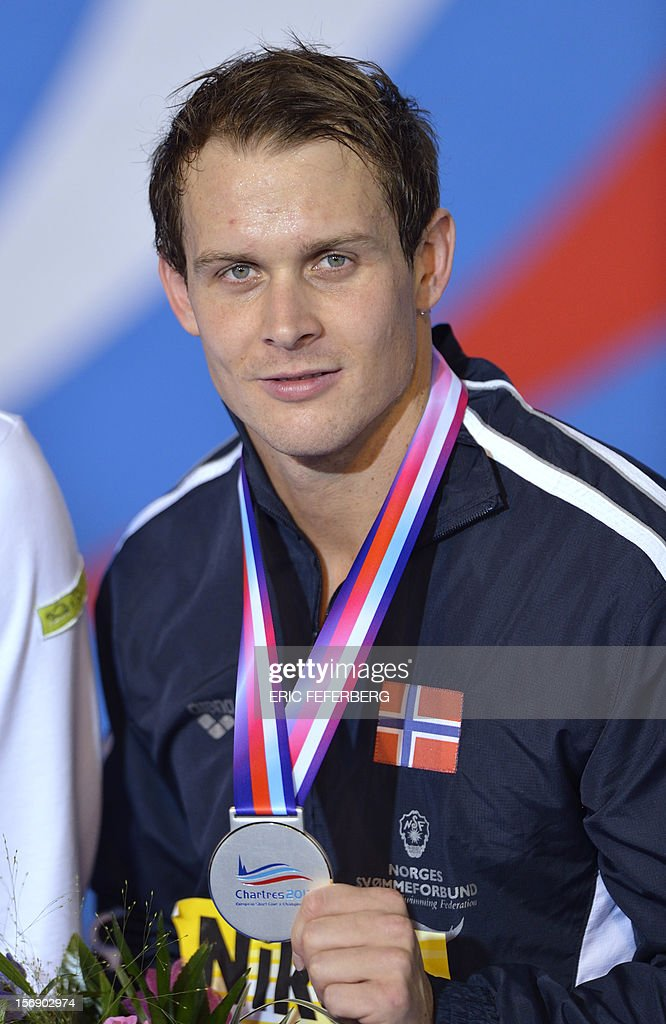 Norwegian swimmer Aleksander Hetland holds his silver medal on the podium of the men's short course 50m breaststroke final at the European Swimming Championships on November 24, 2012, in Chartres.