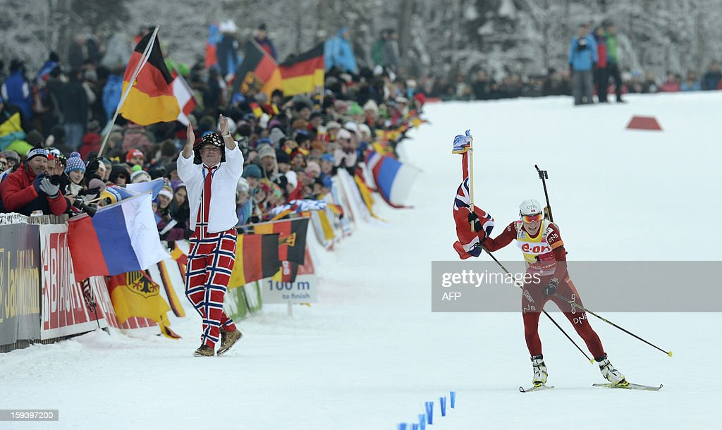 Norwegian Tora Berger gets a Norwegian flag as she arrives at the finish after the 12,5 km women Biathlon World Cup mass start competition on January 13, 2013, in Ruhpolding, southern Germany. Norway's Tora Berger won the competition, Belarus Darya Domracheva placed second and Russia's Olga Zaitseva placed third.