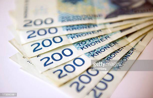 Norwegian two hundred krone currency notes sit in this arranged photograph in Oslo Norway on Friday July 13 2013 Norway's underlying inflation rate...