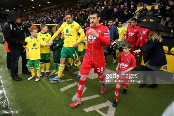 Norwich City Captain Grant Holt [left] and Southampton Captain Adam Lallana lead their teams onto the pitch before kick off of the Barclays...