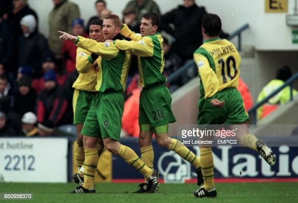 Norwich City's Iwan Roberts celebrates with teammates Darel Russell and Chris Llewellyn after scoring one of his two goals