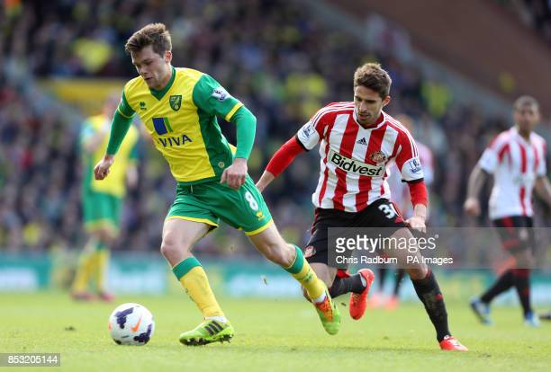 Norwich City's Jonny Howson is challenged by Sunderland 's Fabio Borini during the Barclays Premier League match at Carrow Road Norwich