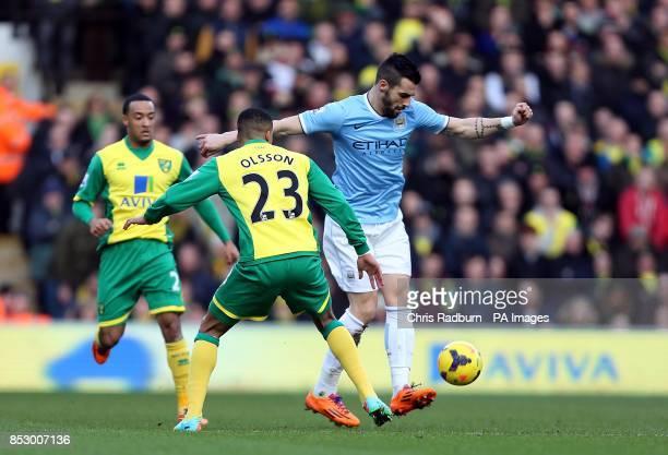 Norwich City's Martin Olsson and Manchester City's Alvaro Negredo battle for the ball