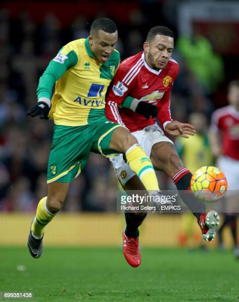 Norwich City's Martin Olsson and Manchester United's Memphis Depay challenge