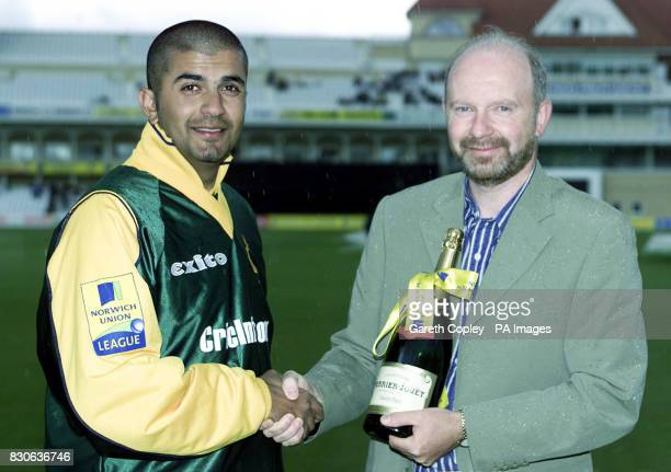 Norwich Union's Regional Sales Manager Steve Whitby presents Nottinghamshire's Usman Afzaal with a magnum of champagne at Trent Bridge Nottingham...