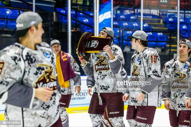 Norwich University players celebrate with the championship trophy after the Division lll Men's Ice Hockey Championship held at the Utica Memorial...