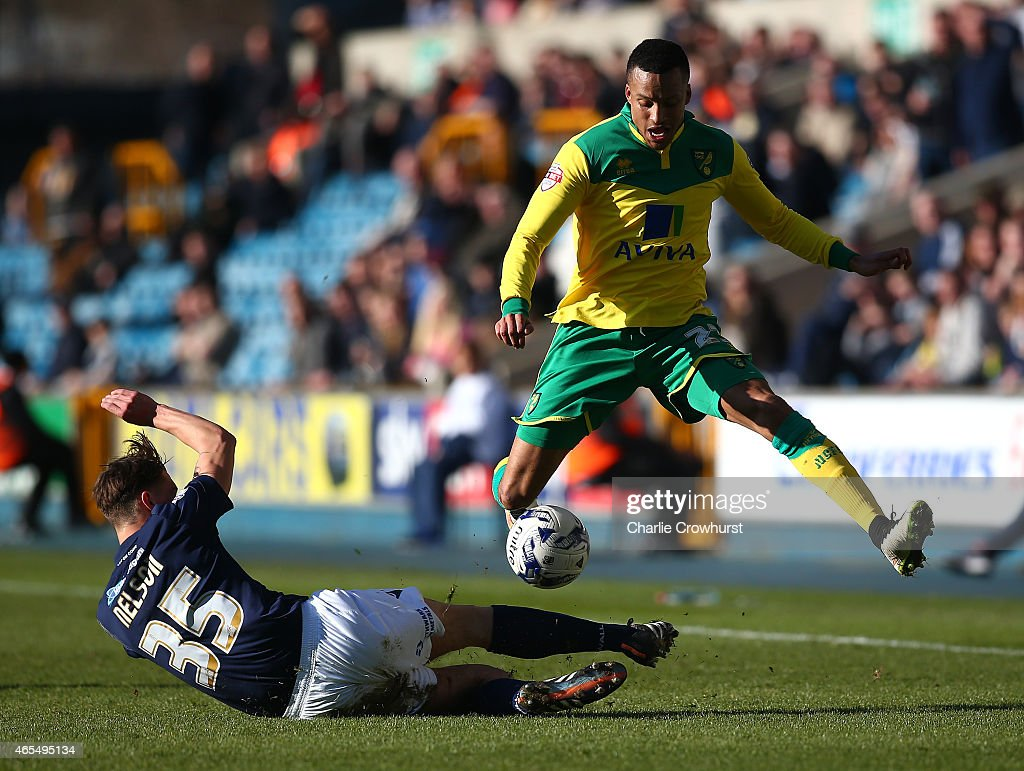 Norwich's Martin Olsson skips the tackle from Sid Nelson of Millwall during the Sky Bet Championship match between Millwall and Norwich City at The Den on March 07, 2015 in London, England.