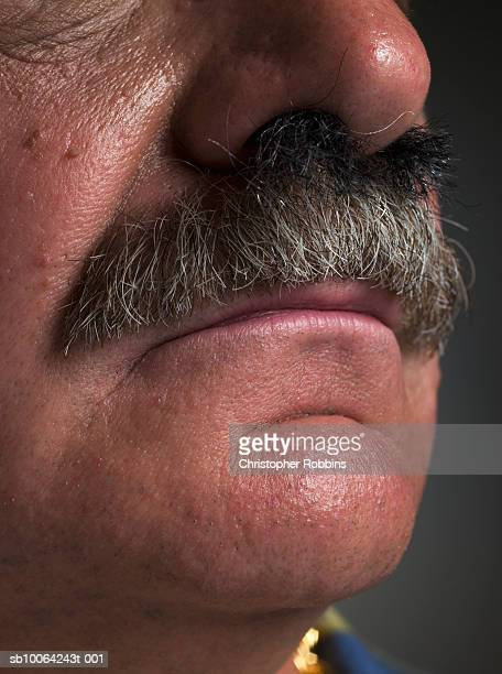 Nose hair growing into senior man's moustache, close-up