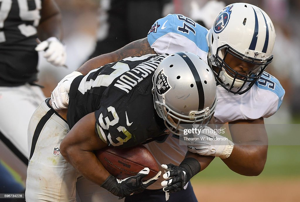 Nose tackle Austin Johnson #94 of the Tennessee Titans tackles running back DeAndre Washington #33 of the Oakland Raiders in the second half of their preseason football game at the Oakland Coliseum on August 27, 2016 in Oakland, California.