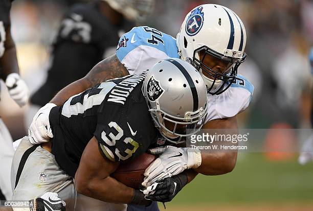 Nose tackle Austin Johnson of the Tennessee Titans tackles running back DeAndre Washington of the Oakland Raiders in the second half of their...