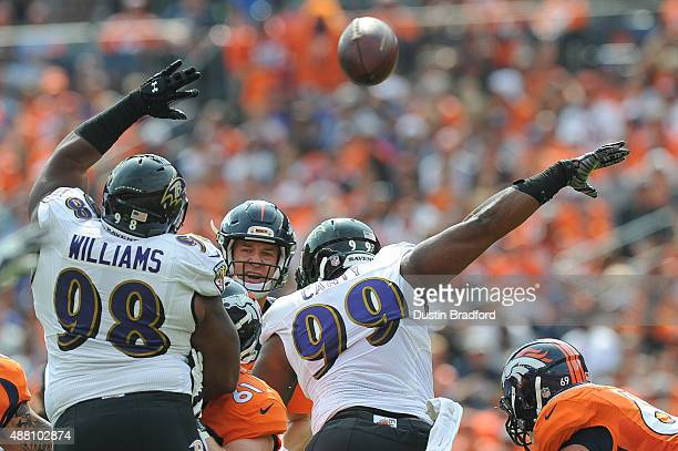 Nose tackle Brandon Williams and defensive end Chris Canty of the Baltimore Ravens attempt to block a pass by quarterback Peyton Manning of the...