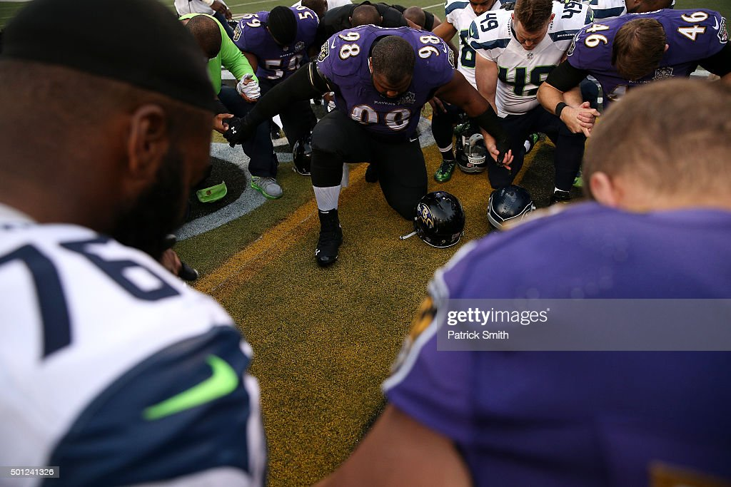 Nose tackle Brandon Williams and long snapper Morgan Cox of the Baltimore Ravens and long snapper Clint Gresham of the Seattle Seahawks take a moment...