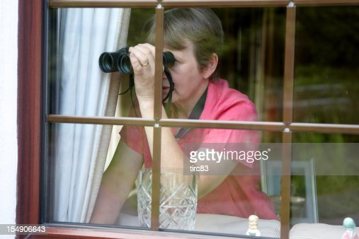 Nosey neighbour at the window with binoculars