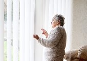 nosey 80 year old senior woman checking up on neighbours, she is standing in front of patio window peering through blinds, could be nosey or just checking everything is safe