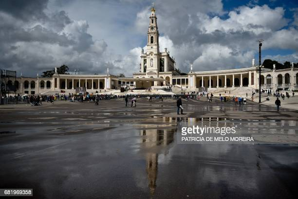 'Nossa Senhora do Rosario de Fatima' basilica reflects on the wet ground at Fatima shrine central Portugal on May 11 2017 Two of the three child...