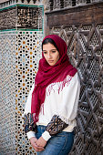 Nostalgic muslim woman in traditional clothing with red hijab and jeans in front of traditional arabesque decorated wall