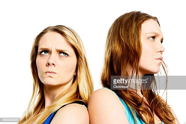 Not happy! Two teenage girls look angry, standing back-to-back