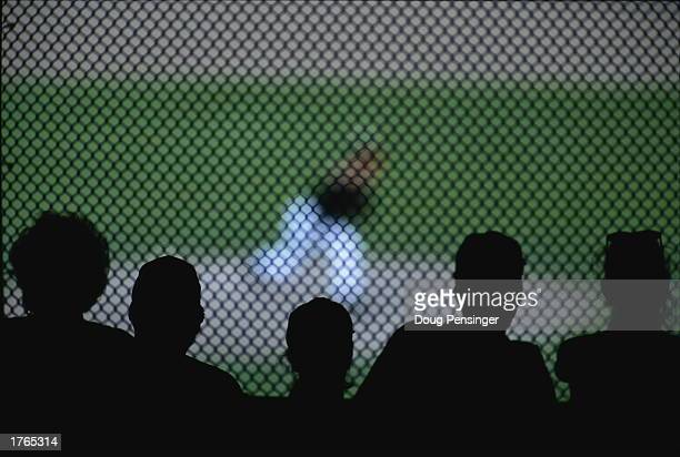 Baseball crowd watching match silhouetted against fence