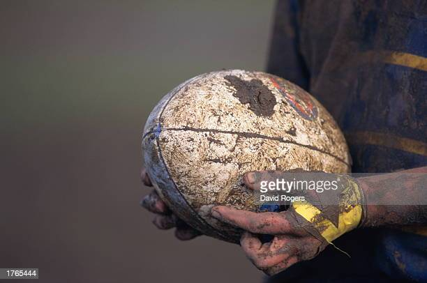 Rugby player''s mudcovered hands holding ball closeup