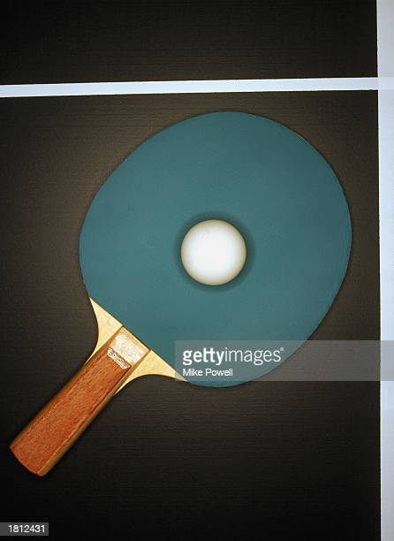Table tennis racquet and ball on table overhead view