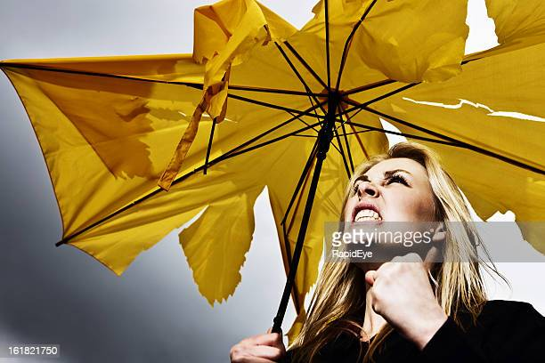 Not singing in the rain: frustrated woman with broken umbrella