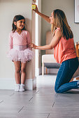 Little girl in a ballet costume having her height measure by her mother. She is standing against the wall whilst her mother uses the tape measure.