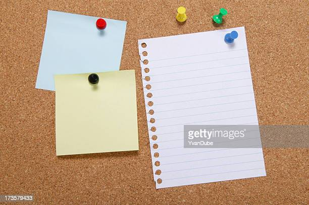 A note board with paper and notes pinned on to it