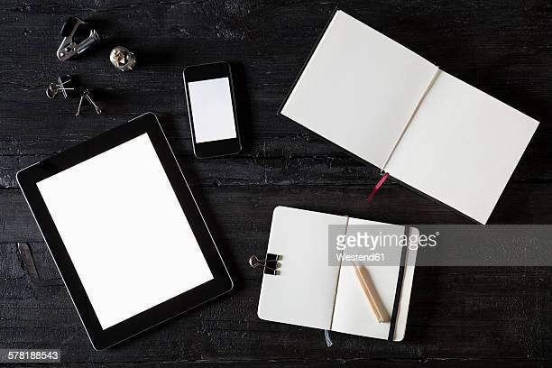Note books, digital tablet, smartphone and tools on black wood