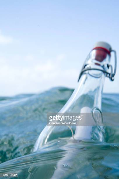 Note in a bottle floating in sea, close-up