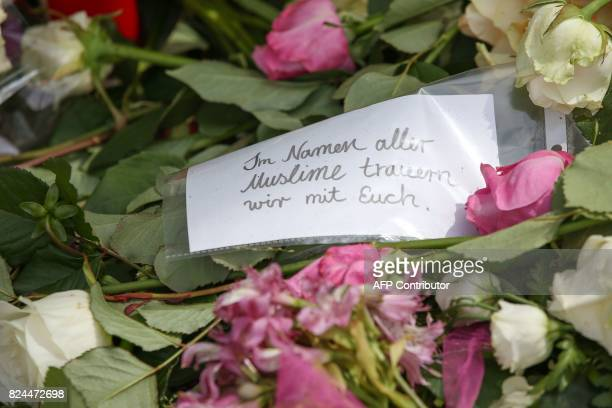 A note reading 'In the name of all Muslims we mourn with you' is placed at a makeshift memorial of flowers on July 30 2017 in front of a supermarket...